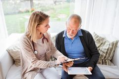Health visitor and a senior man with tablet during home visit. Health visitor and a senior men during home visit. A female nurse or a doctor showing test Royalty Free Stock Images