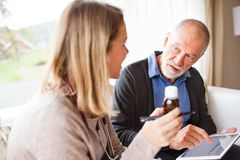 Health visitor and a senior man with tablet during home visit. Health visitor and a senior men during home visit. A female nurse or a doctor showing test Royalty Free Stock Photography