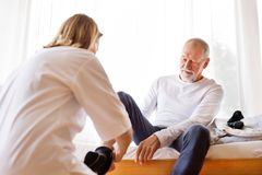 Health visitor and senior man during home visit. Royalty Free Stock Image