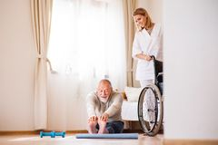Health visitor and senior man during home visit. Health visitor and a senior men during home visit. A nurse or a physiotherapist helping a senior men exercise Royalty Free Stock Photography
