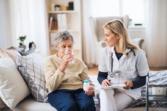 A health visitor and a senior woman at home, taking pills. A young health visitor and a senior women at home, taking pills royalty free stock image