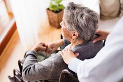 Health visitor and a senior woman during home visit. Unrecognizable nurse giving woman shoulder massage Royalty Free Stock Images