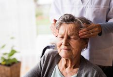 Health visitor and a senior woman during home visit. Unrecognizable nurse giving woman temple massage Stock Photo