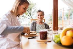 Health visitor and a senior woman during home visit. Health visitor and a senior women during home visit. A nurse and an elderly women sitting at the table Royalty Free Stock Photos