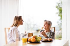Health visitor and a senior woman during home visit. Health visitor and a senior women during home visit. A nurse and an elderly women sitting at the table Royalty Free Stock Image