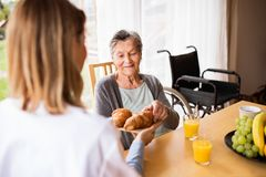 Health visitor and a senior woman during home visit. Royalty Free Stock Photos