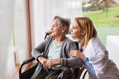 Health visitor and a senior woman during home visit. Health visitor and a senior women during home visit. A nurse talking to an elderly women in an wheelchair Royalty Free Stock Photo