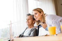 Health visitor and a senior woman during home visit. Health visitor and a senior women during home visit. A nurse talking to an elderly women in an wheelchair Stock Photography