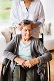 Health visitor and a senior woman during home visit. Health visitor and a senior women during home visit. Unrecognizable nurse giving women temple massage Royalty Free Stock Image