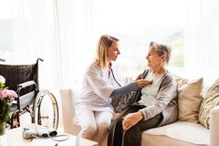 Health visitor and a senior woman during home visit. Health visitor and a senior women during home visit. A nurse or a doctor examining a woman Royalty Free Stock Images
