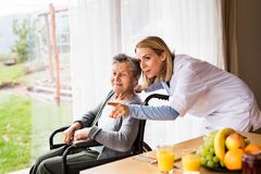 Health visitor and a senior woman during home visit. Health visitor and a senior women during home visit. A nurse talking to an elderly women in an wheelchair Stock Image