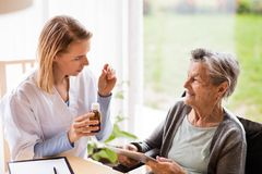 Health visitor and a senior woman with tablet. Health visitor and a senior women with tablet during home visit. A nurse talking to an elderly woman Royalty Free Stock Photo