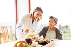 Health visitor and a senior woman during home visit. Health visitor and a senior women during home visit. A nurse pouring orange juice to an elderly woman Royalty Free Stock Photography