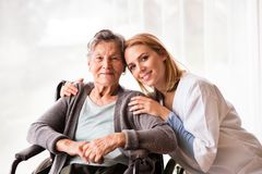 Health visitor and a senior woman during home visit. Health visitor and a senior women during home visit. Portrait of a nurse and an elderly women in an Royalty Free Stock Photography