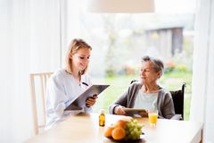 Health visitor and a senior woman with tablet. Health visitor and a senior women with tablet during home visit. A nurse making notes Stock Photo