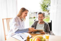 Health visitor and a senior woman with tablet. Health visitor and a senior women with tablet during home visit. A nurse talking to an elderly woman Royalty Free Stock Photography