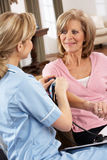 Health Visitor Taking Woman's Blood Pressure Stock Photo