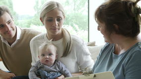 Health Visitor Talking To Family With Young Baby Stock Photo