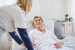 A health visitor talking to a sick senior woman lying in bed at home. A young health visitor talking to a happy sick senior women lying in bed at home stock photography