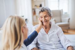 A health visitor talking to a sick senior woman sitting on bed at home. A young health visitor talking to a happy sick senior women sitting on bed at home royalty free stock photo