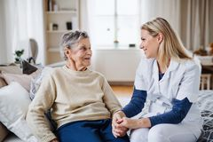 A health visitor talking to a sick senior woman sitting on bed at home. A young health visitor talking to a happy sick senior women sitting on bed at home royalty free stock images