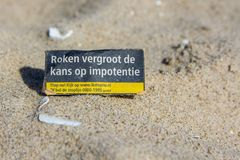 Health warning on cigarette packet left on beach. Kijkduin, the Netherlands - April 6, 2017: health warning on cigarette packet left on beach Royalty Free Stock Photography