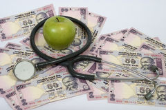 Health is wealth. Fresh apple on top of currency notes, concept health is wealth Royalty Free Stock Photo