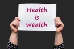 Health is wealth. Motivational sign woman holding by hand stock image