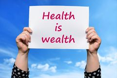 Health is wealth. Motivational sign woman holding by hand royalty free stock photography