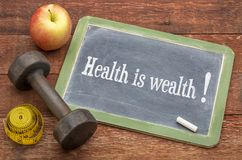 Health is wealth text on blackboard. Health is wealth concept - slate blackboard sign against weathered red painted barn wood with a dumbbell, apple and tape stock images
