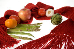 Health winter prevention. A scarf , fruits, vegetables  representing health care through balanced diet and being wrapped warmly Royalty Free Stock Image