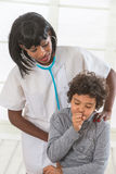 Health worker listens to lungs of young patient in exam room. Female doctor examining little young boy stock images
