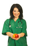 Health worker offering apple Royalty Free Stock Images