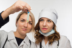 Preparation for giving an injection by the young health workers. Health workers checking the taken biomaterial for allergic reaction Royalty Free Stock Images