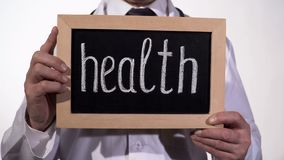Health written on blackboard in doctor hands, healthcare reform presentation. Stock footage royalty free stock photography