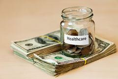 Healthcare. Cost of healthcare. Jar with coins on the dollar bills Stock Photos