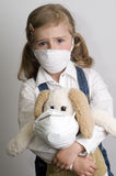 Healthcare. Little girl with toy  wearing a protective mask Royalty Free Stock Photos