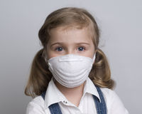 Healthcare. Little girl  wearing a protective mask Stock Photos