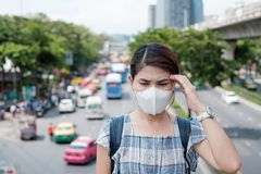 Healthcare and air pollution concept. Young Asian woman wearing N95 respiratory mask protect and filter pm2.5 particulate matter against traffic and dust city royalty free stock images
