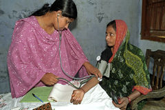 Healthcare in Bangladesh, blood pressure monitor. Bangladesh: Group portrait of Bangladeshi nurse and female patient. The examines the blood pressure of the Royalty Free Stock Images