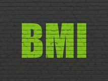 Healthcare concept: BMI on wall background. Healthcare concept: Painted green text BMI on Black Brick wall background Stock Image