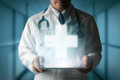 Doctor displays medical cross symbol from tablet. Healthcare Concept - Doctor displays medical cross symbol generated from tablet computer showing future Stock Photo