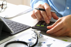Healthcare costs and fees concept.Hand of smart doctor used a ca. Lculator for medical costs in modern hospital Stock Image