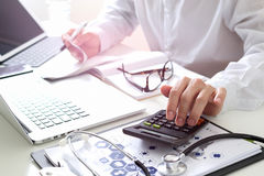 Healthcare costs and fees concept.Hand of smart doctor used a ca. Lculator for medical costs in modern hospital Royalty Free Stock Photography