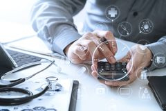 Healthcare costs and fees concept.Hand of smart doctor used a ca. Lculator for medical costs in modern hospital with VR icon diagram Stock Photo