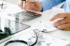 Healthcare costs and fees concept.Hand of smart doctor used a ca Stock Image