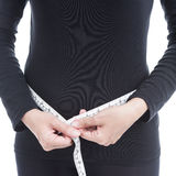 Healthcare and diet concept, woman in black clothes measuring he Stock Images