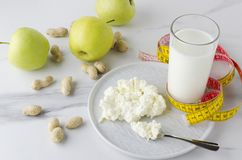 Concept of delicious meal for milk diet and loss weight.Glass of milk,plate with cottage cheese,green apples,peanuts on white tabl royalty free stock photos