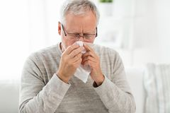 Sick senior man with paper wipe blowing his nose. Healthcare, flu, hygiene and people concept - sick senior man with paper wipe blowing his nose at home stock images