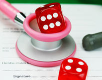 Healthcare Gamble. A Female Doctors pink colored stethoscope with a red dice resting on the top of it, both resting on a doctors sick certificate pad, asking the stock image